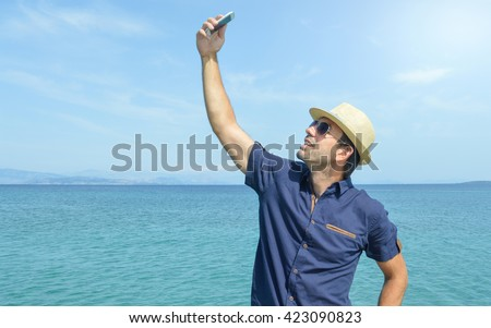 Man Taking A Selfie With His Smart Phone On The Beach - stock photo