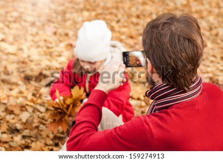 Man taking autumn outdoor picture with mobile phone. Father photograph his girl child playing in the park. - stock photo