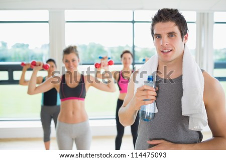 Man taking break from aerobics class with water and towel - stock photo