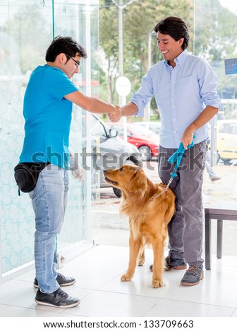 Man taking dog to the vet and handshaking the doctor - stock photo