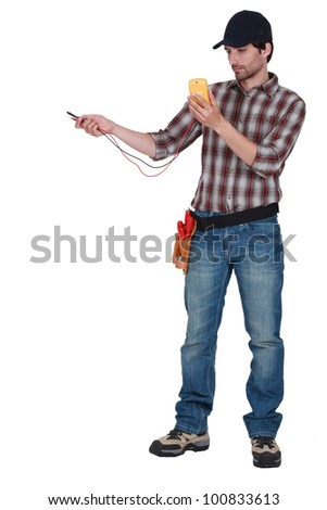 Man taking electrical reading with voltmeter - stock photo