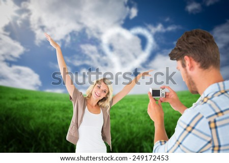 Man taking photo of his pretty girlfriend against green field under blue sky - stock photo