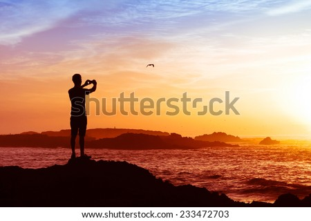 man taking photos of sunset with mobile phone - stock photo