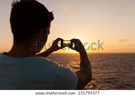 man taking picture of beautiful sunset over sea - stock photo