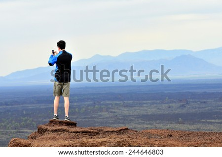 Man taking picture with phone camera of landscape - stock photo
