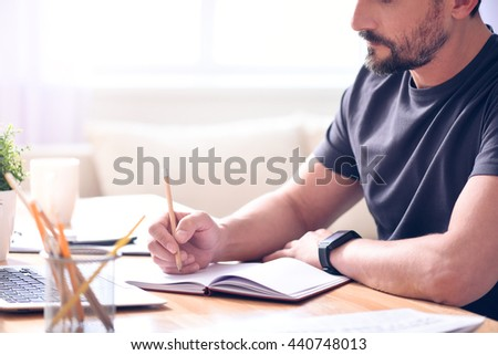 Man taking some notes while sitting - stock photo