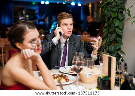 Man talking on a cell phone while on a date with his girlfriend or wife - stock photo
