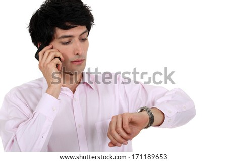 man talking on his cell and watching his watch - stock photo