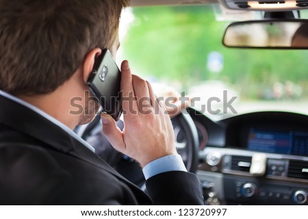 Man talking on the phone while driving his car - stock photo
