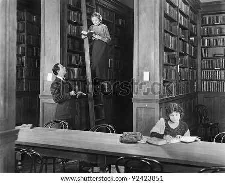 Man talking to a woman standing on a ladder in a library - stock photo
