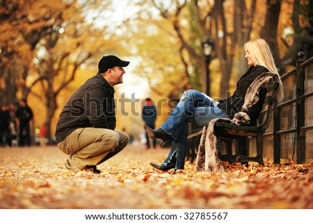 Man talking to hot blond woman in autumn park. Shallow DOF. - stock photo