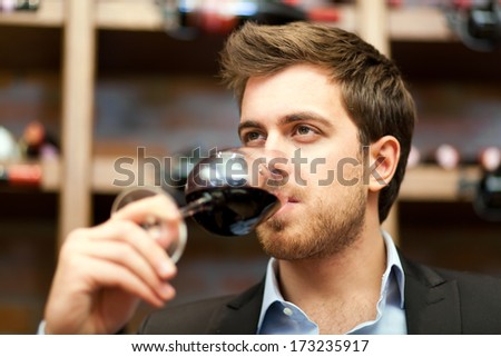 Man tasting a glass of red wine  - stock photo