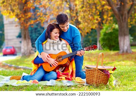 man teaching girl play a guitar on autumn picnic - stock photo