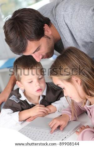 Man teaching kids how to use laptop computer - stock photo