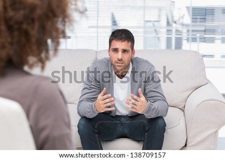 Man telling therapist his problems sitting on the couch - stock photo