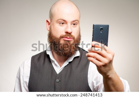 Man texting. Confident young man with long beard in casual wear typing something on his smart phone while standing isolated on studio background - stock photo