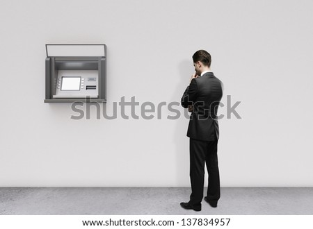 man thinking and looking at atm - stock photo