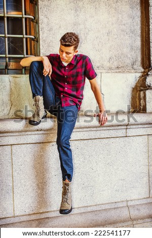 Man Thinking Outside. Dressing in a short sleeve, black, red patterned shirt, jeans, boot shoes, a young handsome guy is sitting by a window, lowering head, looking down at his foot, sad, thinking - stock photo