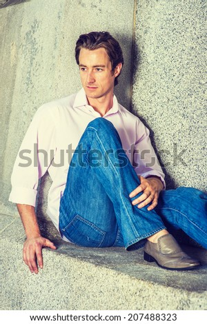 Man Thinking Outside. Wearing a light pink, long sleeve shirt, blue jeans, leather shoes, a young handsome guy is casually sitting against a concrete wall, looking down, thinking  - stock photo
