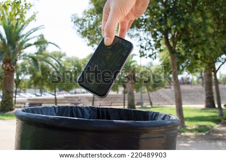Man throwing a phone in the trash - stock photo