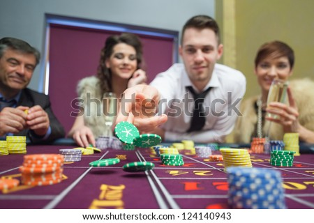 Man throwing chips down on roulette table in casino - stock photo