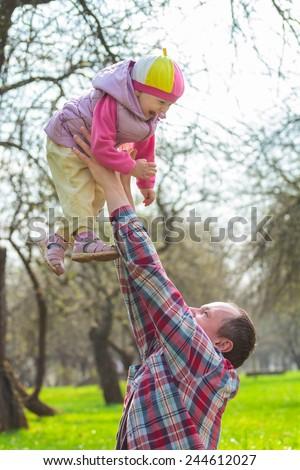 Man throwing up laughing daughter toddler girl - stock photo
