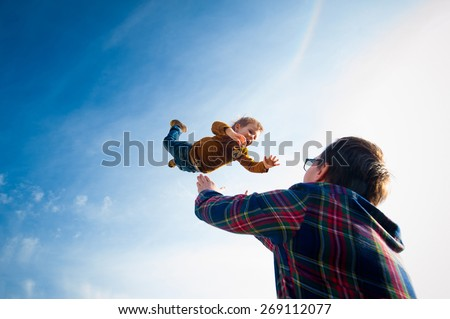 man throws the boy in the sky - stock photo