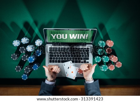 Man thumbs up playing online poker with laptop on a green table with chips all around, top view - stock photo