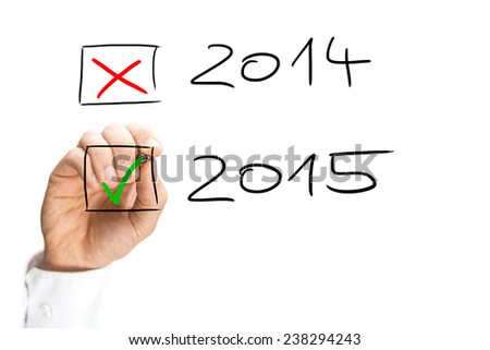Man ticking the start of the 2015 New Year with a green tick in a check box as he crosses off the date for 2014 as the year draws to an end, hand-drawn on a virtual interface. - stock photo