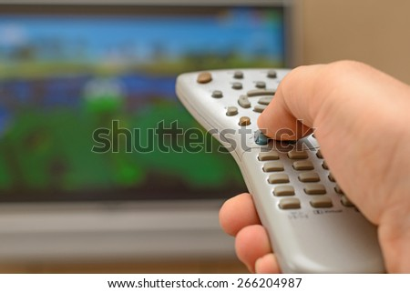 man toggles the the TV remote control - stock photo