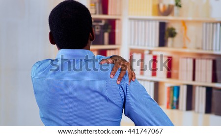 Man touching his shoulder a sign of grief, office pains - stock photo
