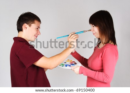 man touching nose of young girl by brush, holding palette, side view - stock photo