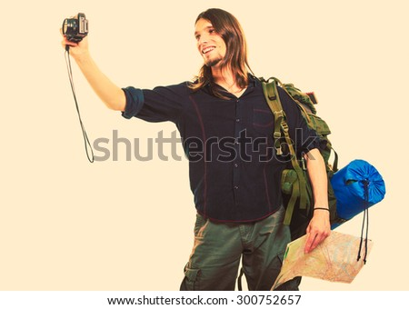Man tourist backpacker on trip taking photo picture with camera. Young guy hiker backpacking holding map. Summer vacation travel. Instagram filtered. - stock photo