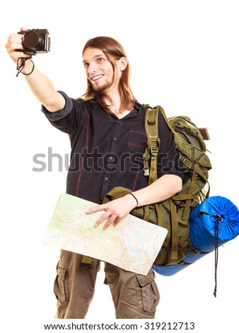 Man tourist backpacker on trip taking photo picture with camera. Young guy hiker backpacking holding map. Summer vacation travel. Isolated on white background. - stock photo