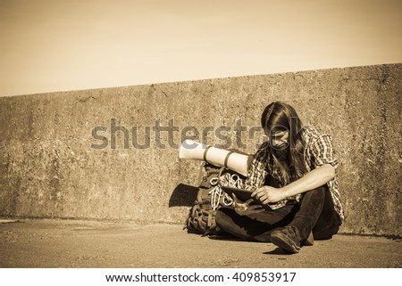 Man tourist backpacker relaxing outdoor sitting by grunge wall using tablet. Internet, tourism active lifestyle. Young hipster guy tramping  - stock photo