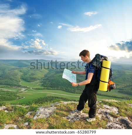 Man tourist in mountain read the map. Leisure activity. - stock photo