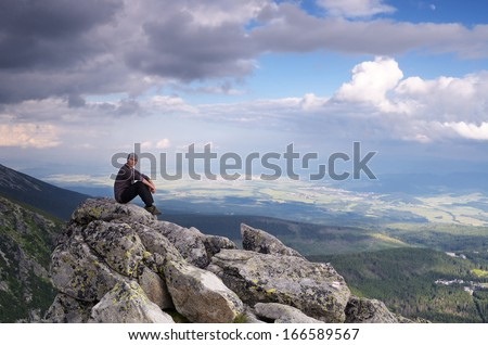 Man tourist is sitting on a rock in the mountains - stock photo