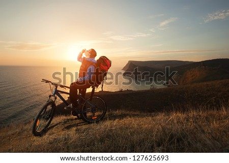 man tourist on a bicycle stopped to have a drink of water at night is very beautiful scenery - stock photo