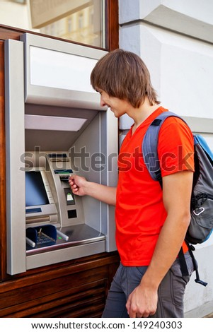 Man tourist puts bank card into the ATM - stock photo