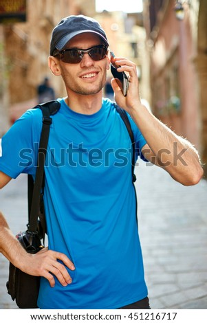 man tourist walking in the old town, and talking by phone, Crete, Greece - stock photo