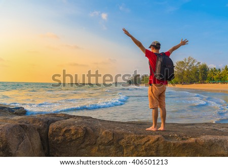 Man tourist with a backpack standing on top of the stone and enjoy the beautiful beach in sunrise time. Phuket,Thailand - stock photo
