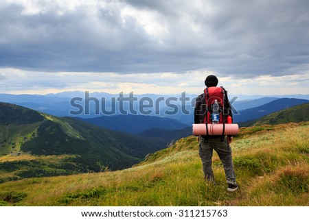 Man traveler hiking in the mountains with a large tourist backpack. Standing back. Admiring the beautiful scenery of Ukrainian Carpathian Mountains. Dramatic cloudy sky. - stock photo