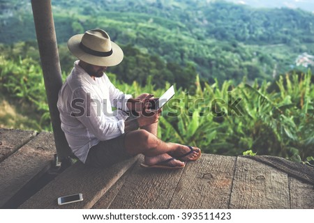 Man traveler is using digital tablet, while is sitting against beautiful Asian scenery during summer journey. Male wanderer is holding touch pad, while is relaxing outdoors during his trip in Thailand - stock photo