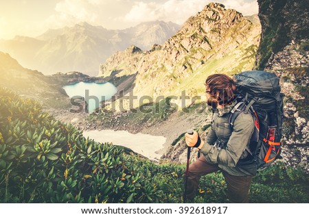 Man Traveler with backpack mountaineering Travel Lifestyle concept lake and mountains landscape on background Summer vacations adventure outdoor  - stock photo
