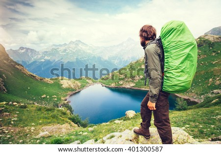 Man Traveler with big backpack hiking Travel Lifestyle concept lake and mountains on background Summer adventure vacations outdoor  - stock photo
