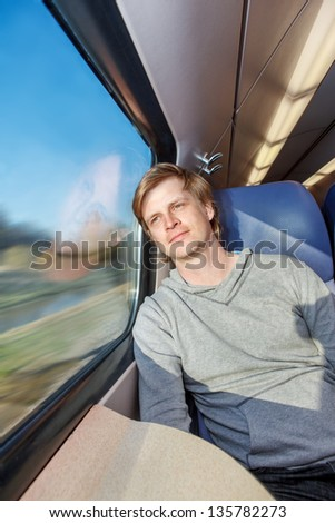 Man traveling by train, looking at the window - stock photo