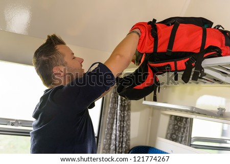 Man traveling by train looking in backpack searching happy vacation - stock photo
