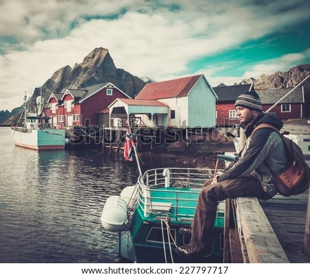 Man traveller sitting on a pier in Reine village, Norway  - stock photo
