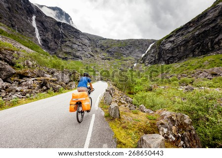 Man travels to Trollstigen pass by bicycle - stock photo