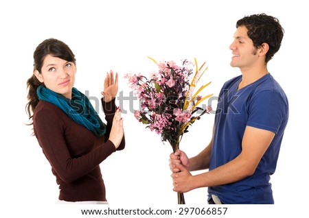 Man tries to give girlfriend flowers but she dimsisses him by holding up her hand and looking upset. - stock photo